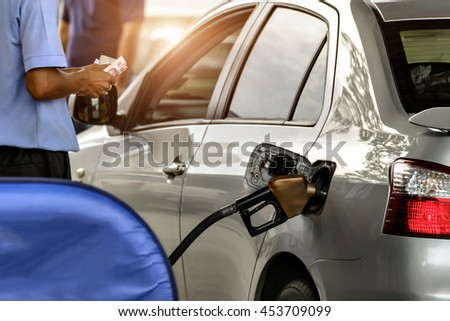 Car refueling on a petrol station and Employees filling, keep cash on hand. - stock photo