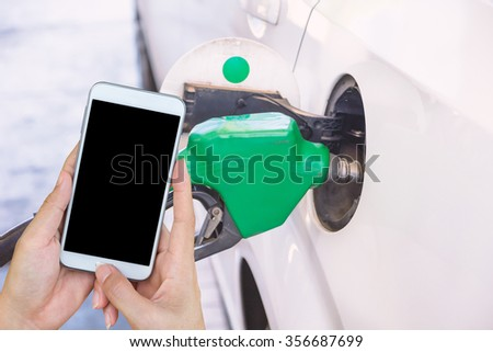 Car refueling on a petrol station. Check oil prices. - stock photo