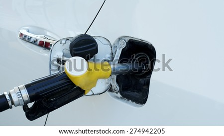 Car Refueling with close up fuel nozzle for transportation concept - stock photo