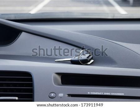 car remote control key laying on car dashbosrd - stock photo