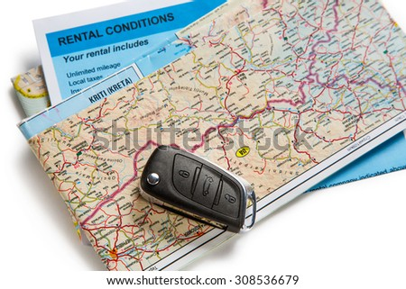 Car remote key on map and rental agreement - stock photo