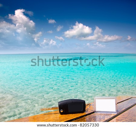 Car rental keys on wood table with blank paper in vacation Caribbean tropical beach [Photo Illustration] - stock photo