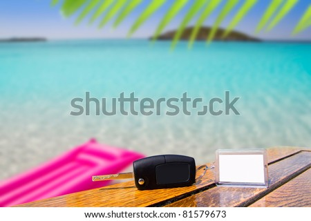 Car rental keys on wood table with blank paper in vacation tropical beach [Photo Illustration] - stock photo