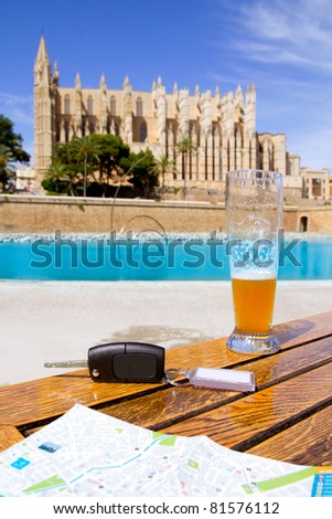 Car rental keys on wood table with city tourist map in Palma de Mallorca cathedral [Photo Illustration] - stock photo