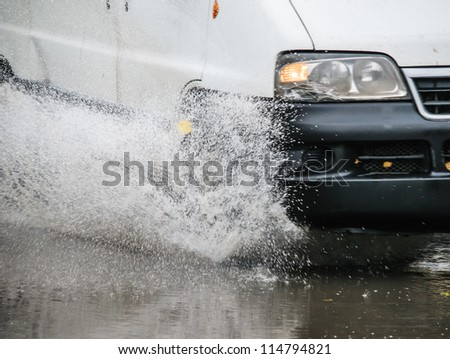 Car rides on big water in the rain - stock photo