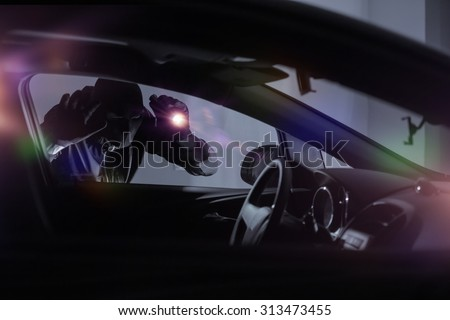 Car Robber with Flashlight Looking Inside the Car. Car Security Theme. - stock photo