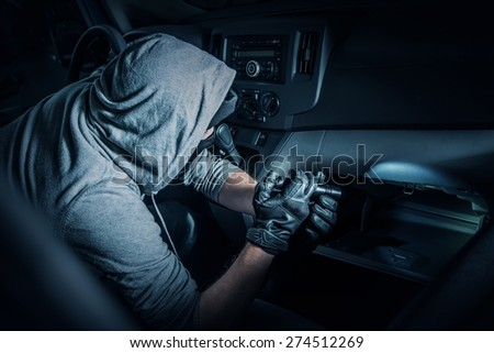 Car Rubber in the Car. Rubber with Flashlight Looking for Valuable Items Inside the Car. - stock photo