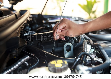 Car's mechanic checking oil.