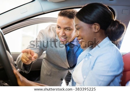 car sales consultant showing a new car to customer - stock photo