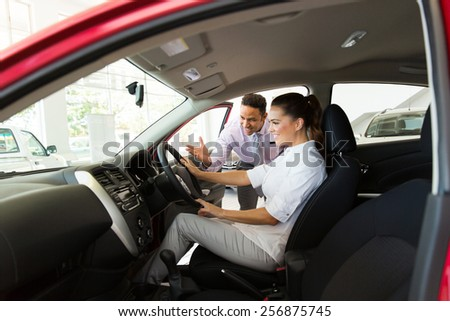 car sales consultant showing a new car to potential customer in showroom - stock photo