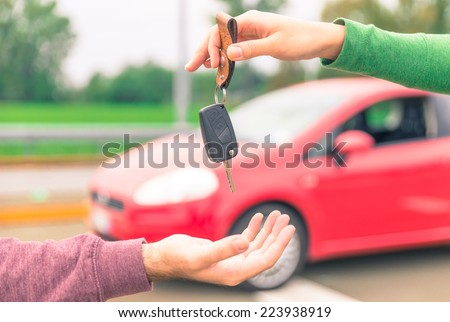 car sales. one person sells car and gives the key to the new owner - stock photo