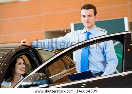 car salesman declares a young girl advantages of the new car - stock photo