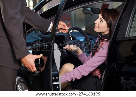 Car salesman giving the car keys to a young woman - stock photo
