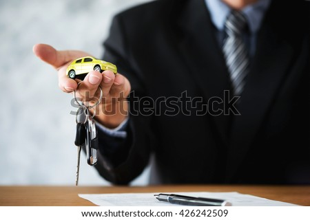 Car salesman giving the key and small model car to the new car owner transportation and ownership concept. - stock photo