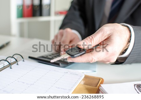 Car salesman holding a key and calculating a price at the dealership office - stock photo