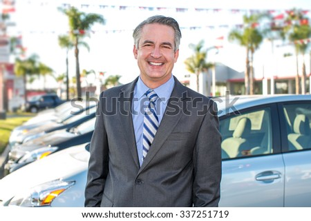 Car salesman standing outside a dealership