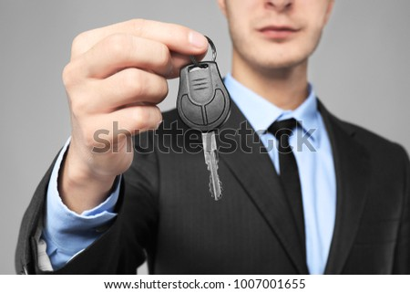 Car salesman with key on grey background, closeup