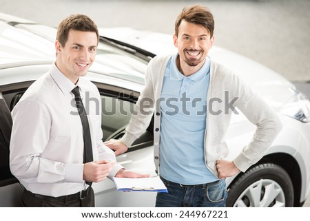 Car salesperson demonstrating a new automobile to young couple. - stock photo