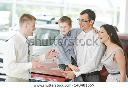 Car salesperson demonstrating new automobile to young family with child - stock photo