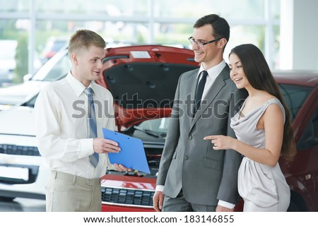 Car salesperson demonstrating rental or new automobile to young woman - stock photo