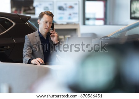 Car salesperson talking on landline phone while working in showroom
