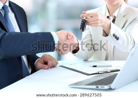 Car saleswoman handing over the keys for a new car to a young businessman . Handshake between two business people - stock photo