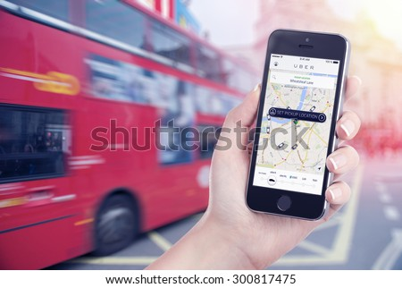 Car search through the Uber app that is displayed on the Apple iPhone screen in female hand. Blurred street view with bus and flare sun light on the background. Varna, Bulgaria - May 26, 2015. - stock photo