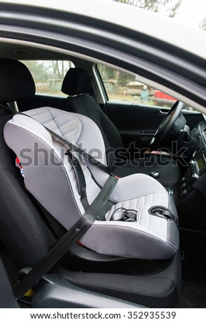 car seat, buckled in the front seat - stock photo