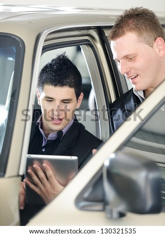 Car seller with car buyer looking at digital tablet
