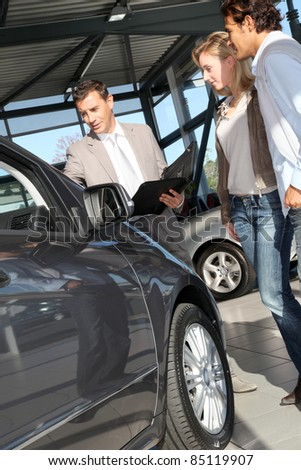 Car seller with couple in showroom - stock photo
