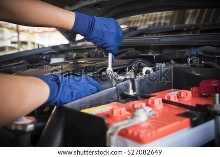 car service fitting a car battery with wrench