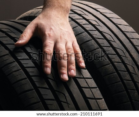 Car service. Wheels and man's hand - stock photo
