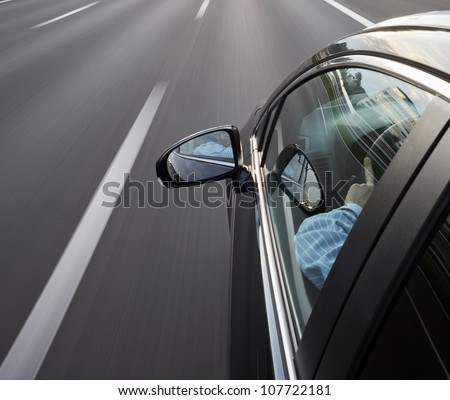 Car speeding along the motorway, with the driver looking in his mirror - stock photo
