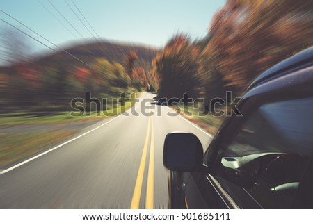 Car speeding on a winding scenic drive upstate New York. The Catskills are one of the most popular destinations for scenic drives, bike trails, foliage and nature lovers