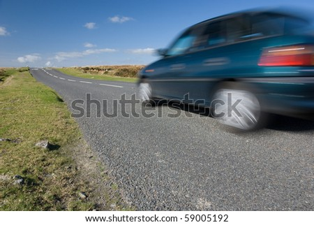 Car speeding on empty road. Dartmoor, UK. - stock photo