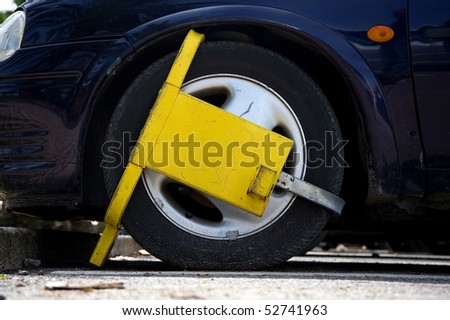 Car street clamped with yellow metal wheel clamp - stock photo