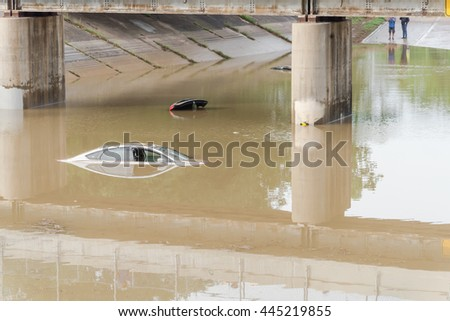 Car swamped by flood water near Buffalo Bayou Park in Houston, Texas. Flooded car under deep water on a heavy high water road. Disaster Motor Vehicle Insurance Claim Themed. Severe weather concept.