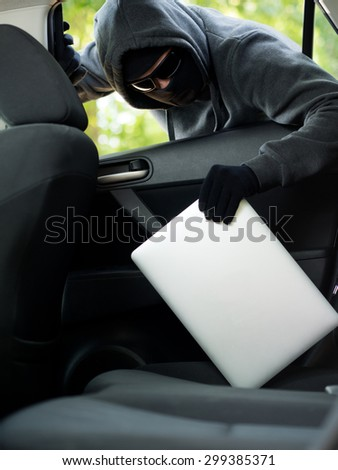 Car theft - a laptop being stolen through the window of an unoccupied car.   - stock photo