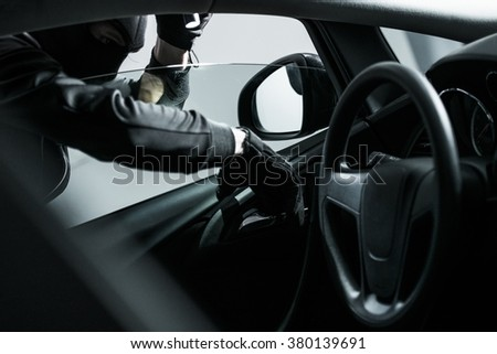 Car Thief Trying to Open Car From the Inside. Car Insurance Concept. - stock photo