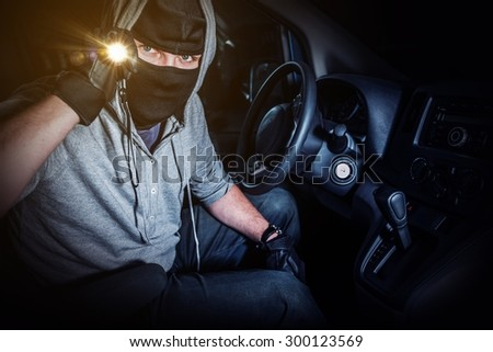 Car Thief with Flashlight Inside Stolen Car at Night. Car Insurance and Protection Concept. - stock photo