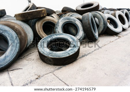car tire heap on cement ground near wall, used tires - stock photo