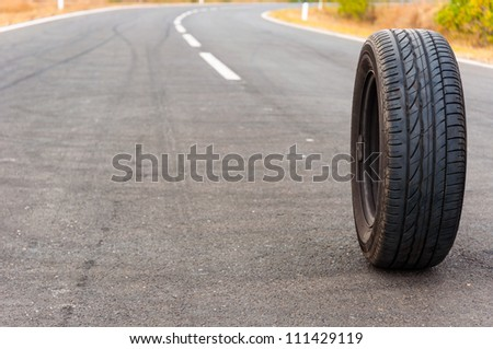 Car tire on the road outdoors - stock photo