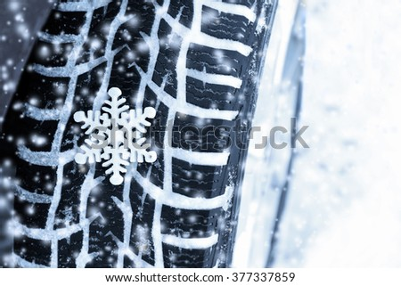 Car tire on winter road - stock photo