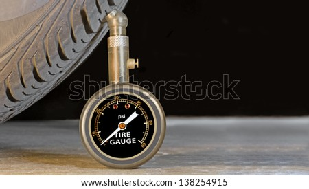 Car tire pressure gauge, tire tread and sidewall close up. Room for text, copyspace. Pressure meter stands upright against tire profile on a grey concrete floor. Black background. - stock photo