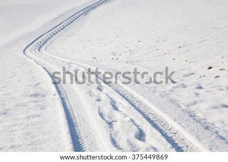 Car tire track and footprints on a empty winter road - stock photo