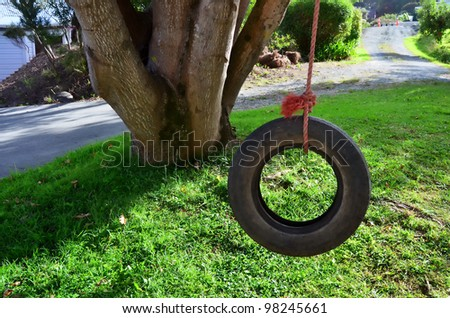Car tire used as a swing on a tree in the garden. Concept photo of childhood, nostalgia, memory , past, life.Concept photo of childhood, nostalgia, memory , past, life, retro, vintage, home sweet home - stock photo