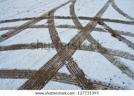 Car tire wheel tracks in different directions on the snow ground - stock photo