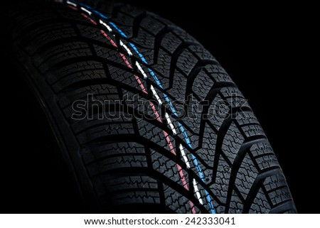 Car tires. Winter wheel profile structure on black background - stock photo