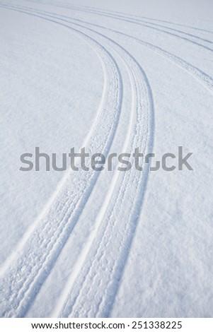 car track on snowy ground - stock photo