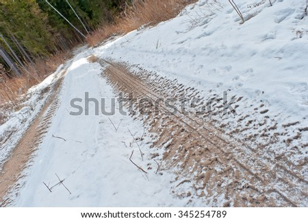 car track on the earth road under snow - stock photo